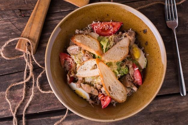 Salade met groenten, kip en kaas in een restaurantplaat