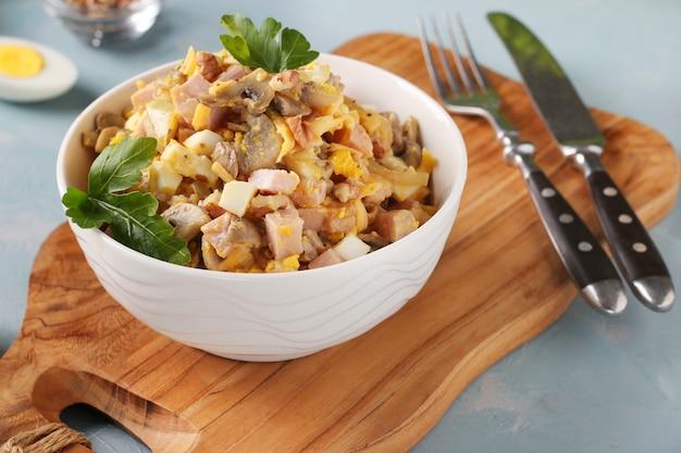 Salade met ham, ei, ui en champignons in een witte kom op een houten bord