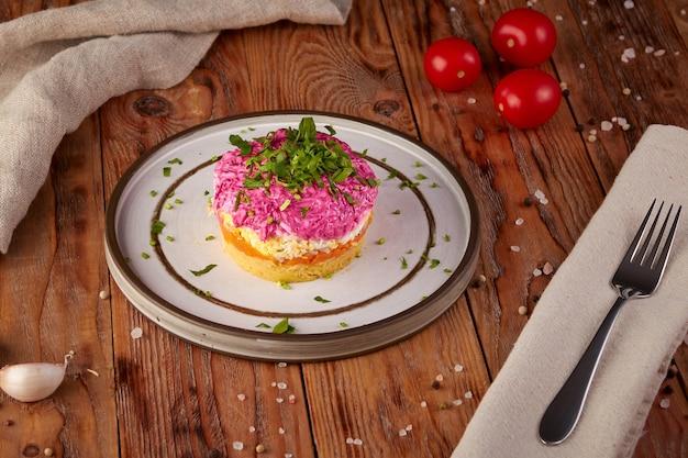 Salade met haring en bieten, russische keuken, houten achtergrond