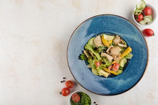 Salade met inktvis. sla, courgette, mini maïs, tomaten, inktvis en saus op een blauw bord op een lichte achtergrond. bovenaanzicht met een kopie ruimte voor de tekst. horizontale oriëntatie.