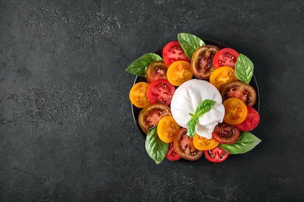 Salade met italiaanse burrata-kaas met basilicum en tomaat op een donkere, gestructureerde achtergrond bovenaanzicht kopie