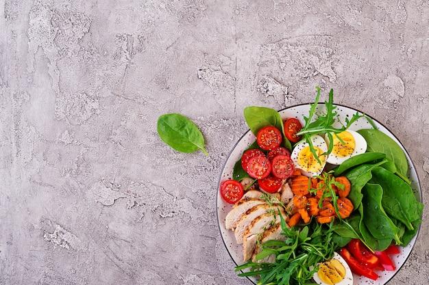 Salade met kerstomaatjes, kipfilet, eieren, wortel, rucola en spinazie