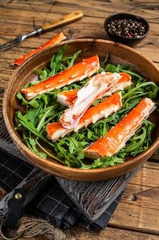 Salade met king crab poten in een houten bord. houten achtergrond. bovenaanzicht.