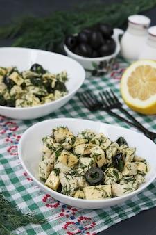 Salade met kip, kaas, dille en zwarte olijven in twee witte kommen op tafel