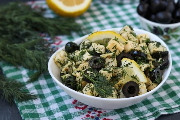 Salade met kip, kaas en zwarte olijven in witte kommen op tafel