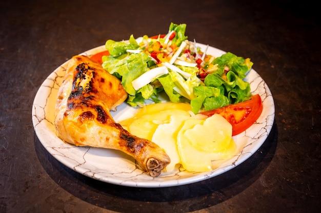 Salade met kippendij en salade op een zwarte achtergrond, op een witte plaat