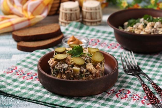 Salade met kippenlever, omelet en ingelegde komkommers op bruine plaat, horizontaal formaat, close-up