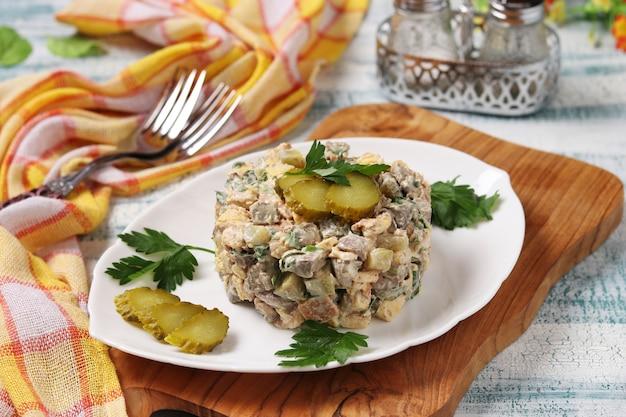 Salade met kippenlever, omelet en ingelegde komkommers op witte plaat, horizontaal formaat