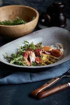 Salade met krab en avocado op een donkere achtergrond. rucola salade bladeren gekruid met saus op witte wijn met krab vlees en gegrilde avocado in soft focus.