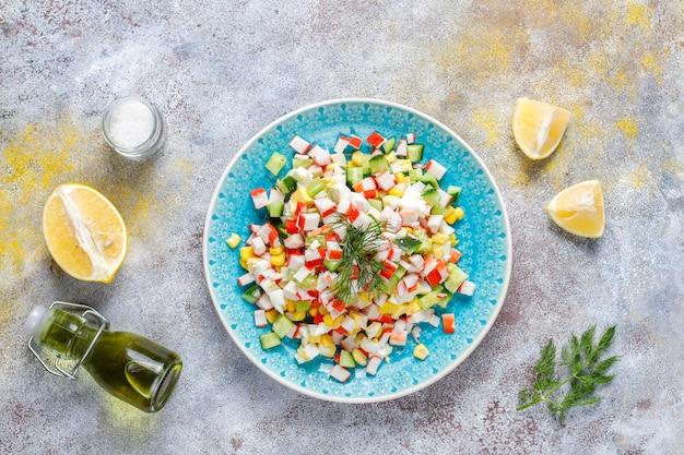 Salade met krabsticks, eieren, maïs en komkommer.