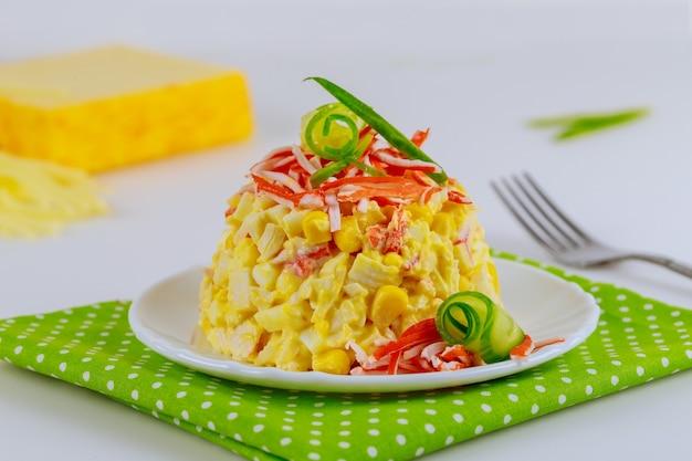 Salade met krabstokken, komkommer, eieren en maïs op witte plaat met vork.