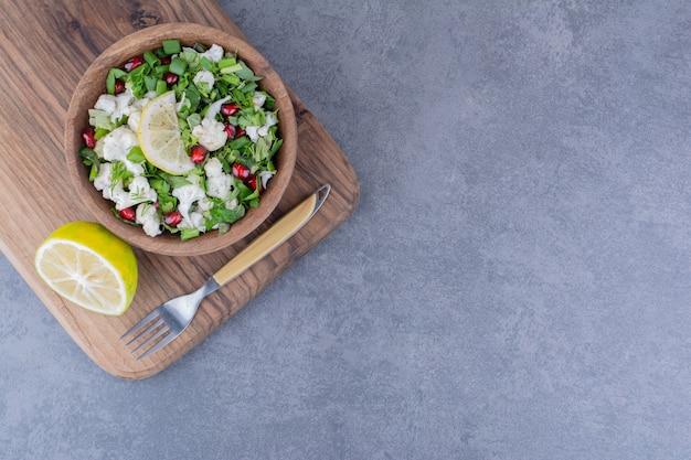 Salade met kruiden, fruit en groenten in een schotel