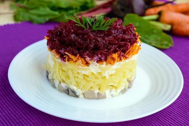 Salade met lagen gekookte groenten en gezouten vis