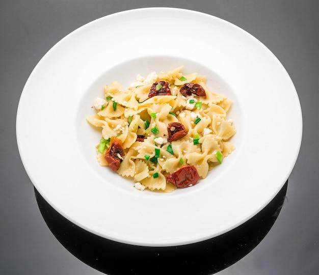 Salade met macaroni, pesto, olijven, zongedroogde tomaten en rozemarijn
