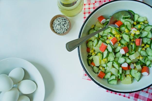 Salade met maïs, krabstokken, komkommers in een witte kom op een witte achtergrond.