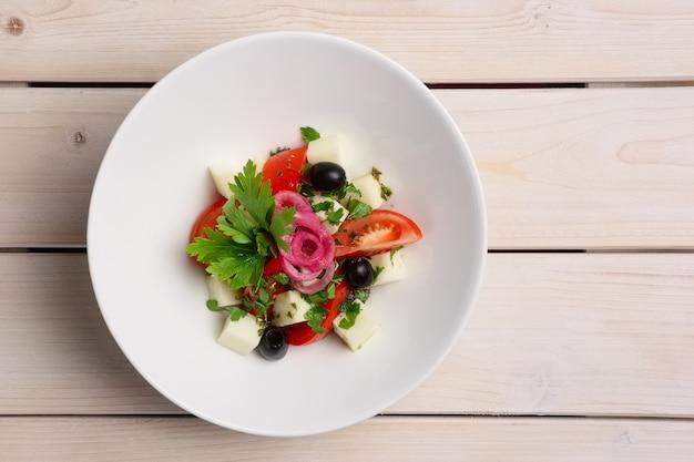 Salade met mozarella, tomaat en olijven. bovenaanzicht.