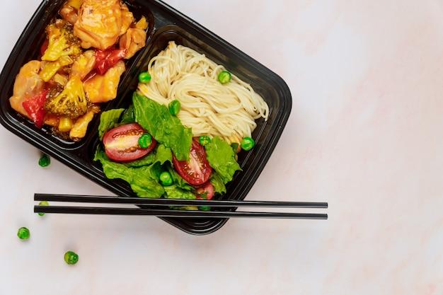 Salade met noedels en kip in zoetzure saus op voedsel plastic dienblad.