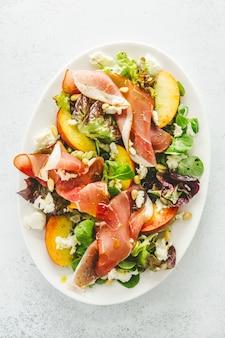 Salade met perziken, ham en kaas geserveerd op plaat.
