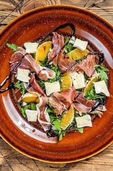Salade met prosciutto parmaham, parmezaanse kaas, rucola en mandarijn op een bord. houten tafel. bovenaanzicht.