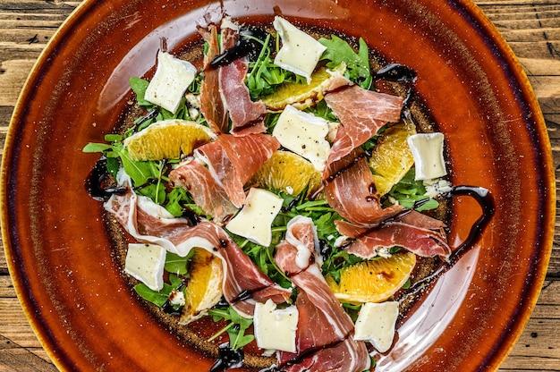 Salade met prosciutto parmaham, parmezaanse kaas, rucola en mandarijn op een bord.