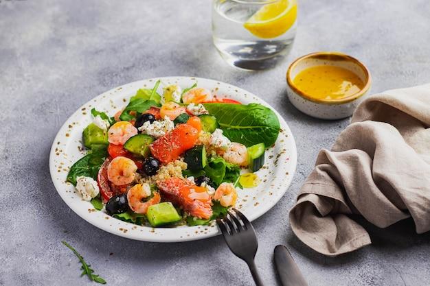 Salade met quinoa, ijsbergsla, rucola, komkommer, zwarte olijven, tomaat, kwark, zalm, garnalen en mangosaus geschroeid op grijze muur. schoon eten voor het versterken van de immuniteit