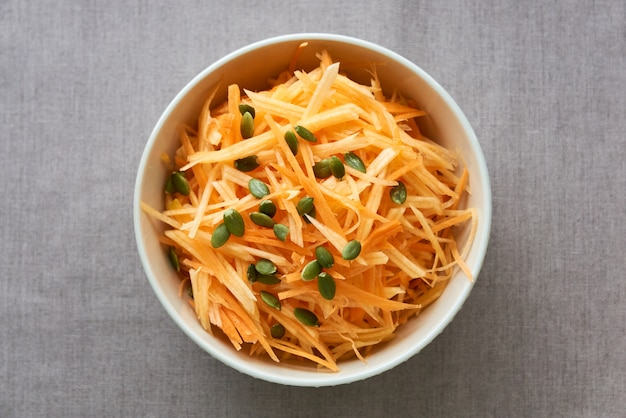 Salade met rauwe pompoen en wortelen in een witte kom
