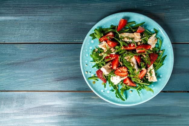 Salade met rucola, aardbeien en kaasbrie, camembert. lang bannerformaat. ruimte voor tekst. bovenaanzicht