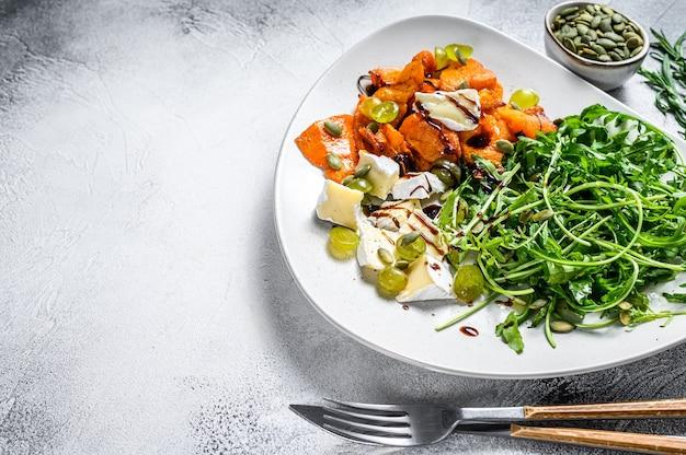 Salade met rucola, gebakken pompoen en brie. witte achtergrond. bovenaanzicht. ruimte kopiëren.