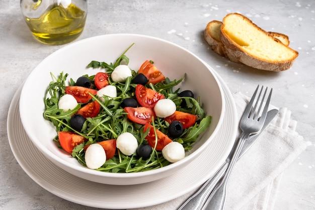 Salade met rucola mozzarella tomaten en olijven, olijfolie en vers brood