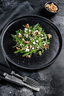 Salade met rucola, noten, fetakaas, olijfolie, kruiden. zwart oppervlak. bovenaanzicht