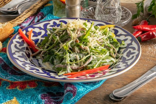 Salade met rundvlees tong, rucola, kaas en paprika in een keramische plaat met traditionele oezbeekse ornamenten op een houten tafel naast bestek met een mes en vork.