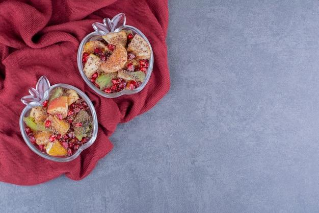 Salade met seizoensfruit en kruiden op betonnen ondergrond