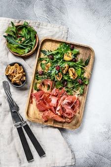 Salade met serrano jamon, ham, rucola en vijg. antipasto., bovenaanzicht.