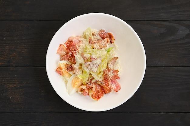Salade met spek, ei, kool en geraspte kaas op donkere houten tafel