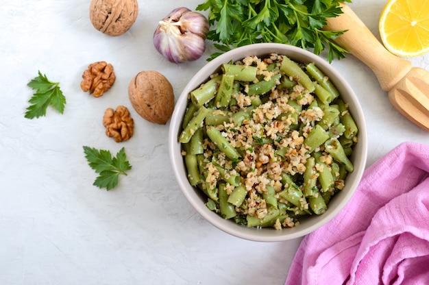 Salade met sperziebonen en pittige walnootsaus in een kom. vegetarisch, veganistisch menu. bovenaanzicht.