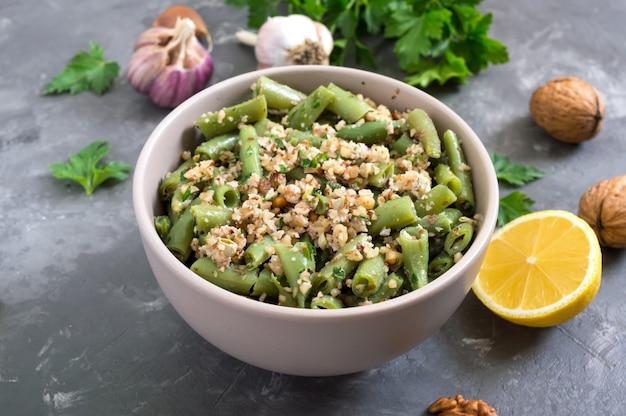 Salade met sperziebonen en pittige walnootsaus in een kom. vegetarisch, veganistisch menu.