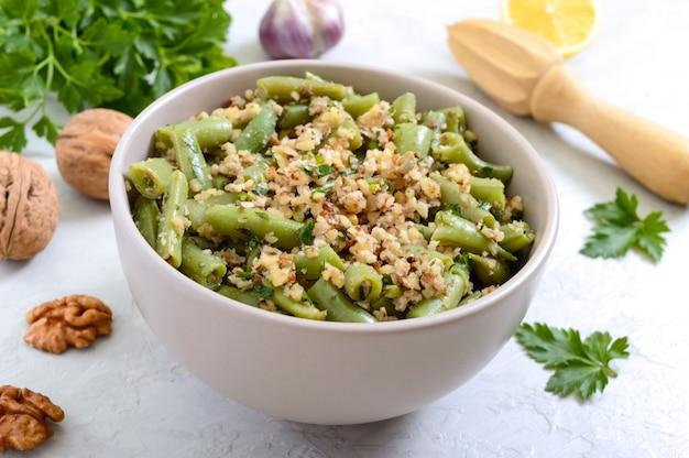 Salade met sperziebonen en pittige walnootsaus in een kom. vegetarisch, veganistisch menu