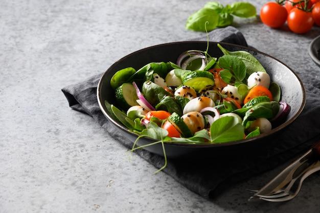 Salade met spinazie, cherrytomaatjes, ui en mozzarella op grijze stenen achtergrond.