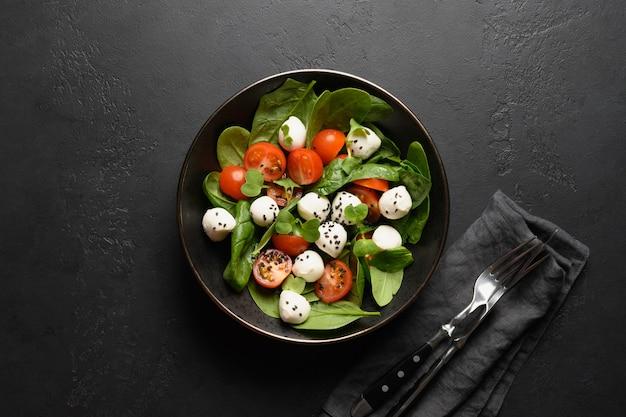 Salade met spinazie, kerstomaatjes, ui en mozzarella op zwarte stenen achtergrond