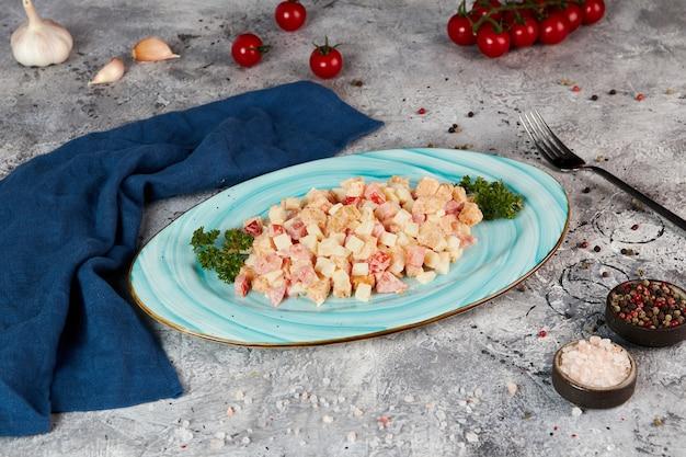 Salade met tomaten, croutons en romige saus, grijze achtergrond