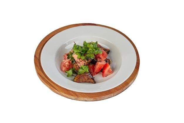 Salade met tomaten en aubergines op wit wordt geïsoleerd