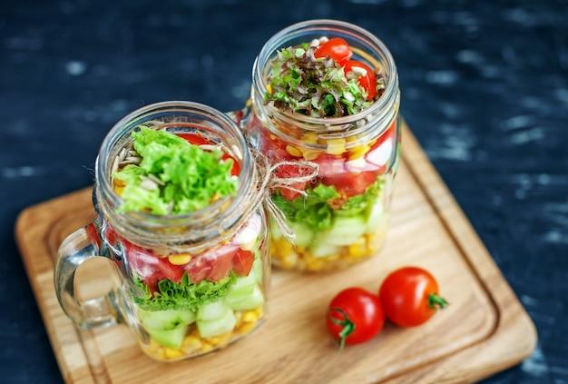 Salade met tomaten en komkommers en maïs in een glazen pot.