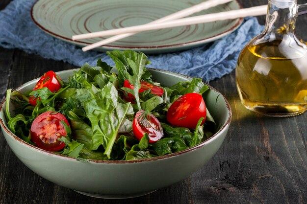 Salade met tomaten, rucola en spinazie op een zwarte houten tafel