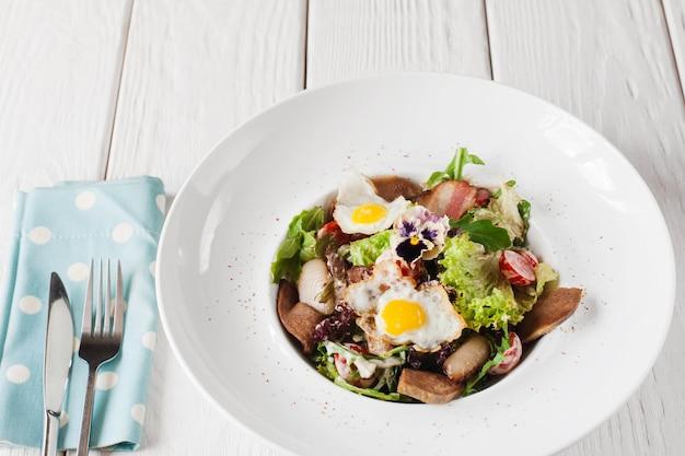 Salade met tong en kwarteleitjes op witte houten