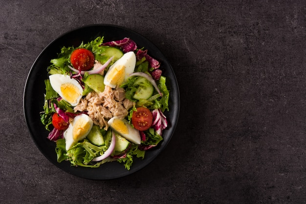 Salade met tonijn, ei en groenten op zwart