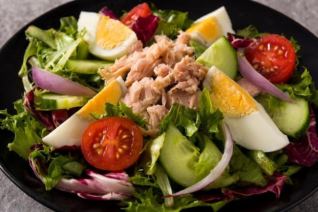 Salade met tonijn, ei en groenten op zwarte plaat