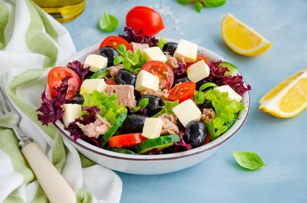 Salade met tonijn, verse groenten, olijven en fetakaas in een kom. gezond eten.