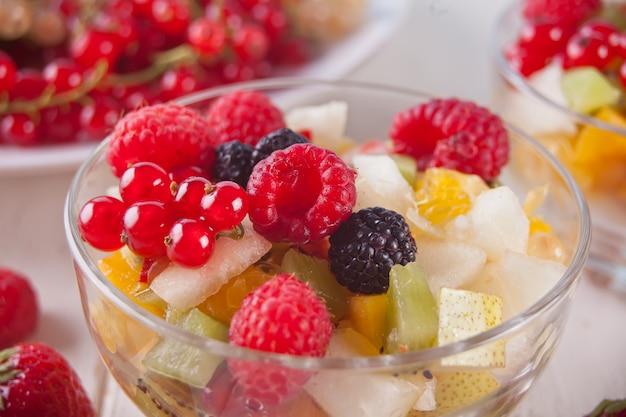 Salade met vers fruit en bessen op kommen op de witte achtergrond