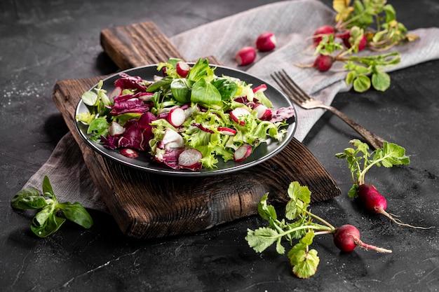 Salade met verschillende ingrediënten op donkere plaat