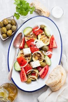 Salade met verse en gegrilde salade op witte schotel op grijze keramiek